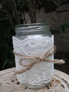 small vase /jar covered with lace and tied with jute.  Simple and swee.