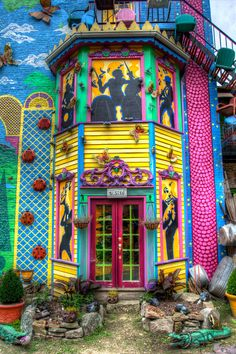 Vibrantly painted building with red double doors and party scenes Colourful Buildings, Beautiful Buildings, Beautiful Homes, Beautiful Places, Colorful Houses, Deco Boheme, Door Knockers, Windows And Doors, House Colors