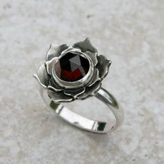 Lotus of the Heart Sterling Silver and Garnet Ring.    A deep red rose cut garnet is set in an opening lotus flower. Garnets are said to attract love,
