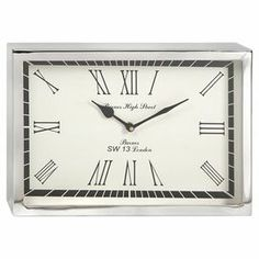 """Crafted from stainless steel and showcasing a sleek silhouette, this clean-lined wall clock adds contemporary appeal to your home office or kitchen.  Product: Wall clockConstruction Material: Stainless steel and glassColor: Silver and whiteFeatures: Sleek silhouetteAccommodates: Batteries - not includedDimensions: 8"""" H x 12"""" W x 2"""" D"""
