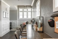 Well appointed hallway homework room features windows framed by gray textured wallpaper and positioned above three gray chairs facing a wood desk top lit by teardrop task lamps as marker bins and pin boards hang from hooks above the desk.