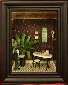 French Cafe vignette in a black picture frame with a table and chairs, palm, and wooden butler.
