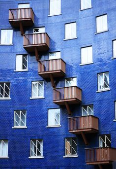 The distinctive facade of a curved blue building with iron rail balconies and white windows in London.