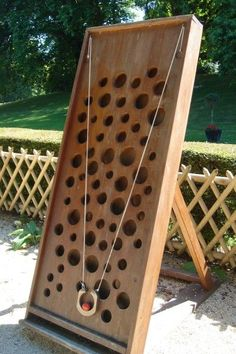 Pull the two strings _carefully_ to try to get the ball to the top without dropping it through a hole. - Jeux en bois- Neat looking Game