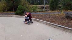 padre le enseña a andar en patineta a su hijo