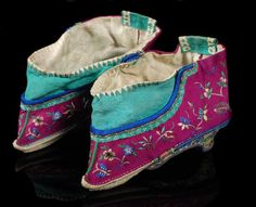 A pair of Chinese silk shoes for a woman`s bound feet, of silk damask, with pointed toe, embroidered with floral designs and gold thread, late 19th-early 20th century, 11.5cm wide