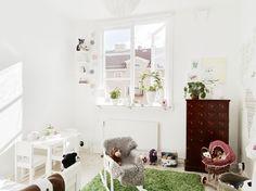 biały stolik i krzesełka dziecięce, brązowy szufladnik,biały fotelik na płozach i zielony dywan z długim włosem - Lovingit.pl