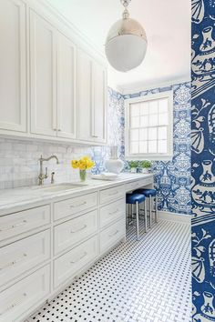 Bear Hill Interiors - A long laundry room features a Hicks pendant over walls clad in David Hicks The Vase Wallpaper in Blue lined white shaker cabinets adorned with nickel hardware paired with honed white marble countertops and a carrera marble subway tiled backsplash.