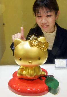A Japanese woman looks at a pure gold Hello Kitty doll at the opening of the Gold Expo at Tokyo's Matsuzakaya department store. The 100 cm tall panda figure is on sale with a price of 8.88 million yen (88,000 USD), and the gold products exhibition will be held through February 25.