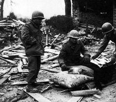 Soldats américains aident une vieille femme belge, qui ont refusé d'évacuer la ville, Manhay, au cours des combats. American soldiers help an old Belgian woman, who refused to evacuate the town, Manhay, during the fighting.