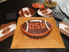 I used 2 yellow cake mixes, baked in rectangle sheet pan, then cut in shape of football. Iced with chocolate icing, put kit kats around sides (I used the small ones) then used reeces pieces on the top.