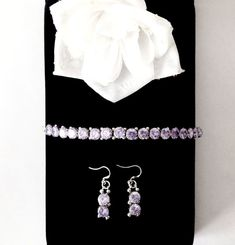 One of a kind 7.25 inch tennis bracelet set features a series of 2 carat diamond cut blue violet Cubic Zirconia with sterling silver embellishments and findings. Comes with coordinating earrings.