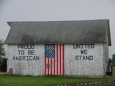 United we stand. Proud to be an American. White barn with the American flag painted on it.