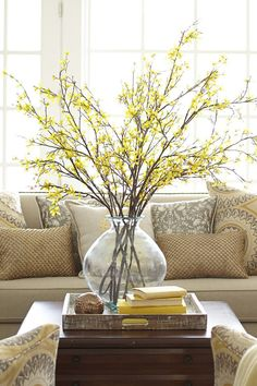 Tap into your country side with this yellow and beige room combination. Brighten up the room with a bunch of yellow long stemmed flowers and wooden centerpieces that just work well together. The centerpiece arrangement also complements with the beige sofa and copper cushions.