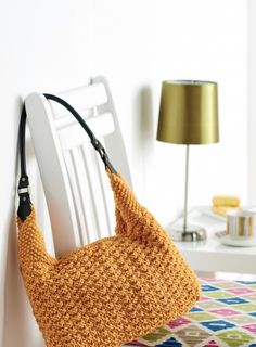 In a stylish golden yarn and with a faux leather shoulder strap, Lucinda Ganderton's textured knit handbag is both trendy and practical. The design incorporates sewing when making the lining but if you're not a sewer, don't fret, our instructions