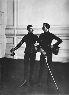 modernfencing:  [ID: two men in old-style fencing uniforms, with linked arms and sabres. Old, black and white photo.] Awkwardly translated f...