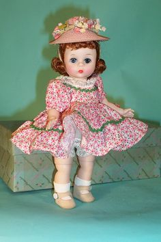 """American Princess Doll - """"Dressed for A Summer Day"""" of 1962 in a ruffled cotton dress, printed with tiny bright pink asters. Elegant little pink straw hat trimmed with tiny lilies of pastel shades."""