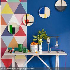 Retro-Look entsteht durch diese kunterbunte Mustertapete mit dreieckigen Mosaikteilchen. Ergänzt wird der Retro-Look durch die an der Wand hängenden Teller…