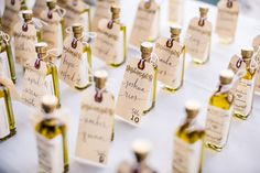 Mini bottles of olive oil serve double-duty as #weddingfavors and name cards! Creative! {Kreate Photography & Design}