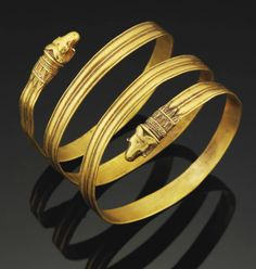 A GREEK GOLD BRACELET HELLENISTIC PERIOD, CIRCA 4TH-3RD CENTURY B.C. Formed from a strap coiled spirally, flat on the interior, ridged on the exterior, with two terminals in the form of ram heads with curving ribbed horns, tufts of hair incised on their foreheads, each emerging from a beaded collar with plaited filigree decoration, row of tongues below, and three spear-shaped leaves extending over the hoop