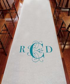 Classic Deco Monogram Wedding Aisle Runner made of white non-woven fabric that is resistant to tearing. The design centers around your three letter monogram, with the center last name inital decorated with elegant scroll work accents. This aisle runner comes with an attached pull cord handle and double-sided adhesive tape to secure it in place.