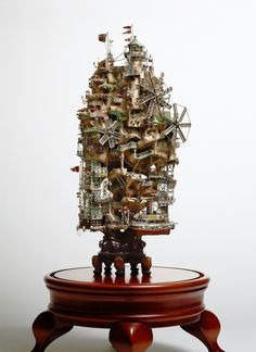 Using craft paper, plastic, plaster, acrylic resin, paint and other materials Aiba constructs sprawling miniature communities that wrap around bonsai trees, lighthouses, and amongst the cliffs of nearly vertical islands.