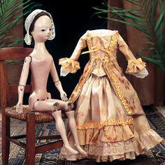 English wooden doll circa 1760, included are her original quilted petticoat and stays, hip-length hoop, skirt coin purse, kid slippers, along with a later silk gown