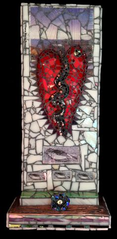 photo of glass mosaic heart. the heart is red with a zigzag stripe down the middle with nails in it. It is on a white glass background,but the upper portion has a photo under transparent glass. It is a very purple photo of the coast of Maine. On the bottom there is an altar like protrusion with a flower like vase turned on its side facing the audience. the vase is made from dichroic glass so looks rainbow like with an emphasis on colors in the blue/indigo spectrum!!!