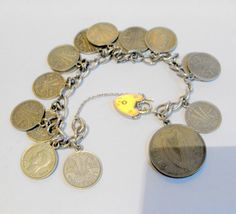 B11244 £25 inc UK post. Offers welcome. A vintage charm bracelet consisting of various coins attached to a silver tone chain (there is some marking on one of the links but we have been unable to decipher it), the coins being primarily Australian silver threepences dating from the 1940s and 1950s, with a few other silver metal coin. The bracelet is fastened by means of a Sterling Silver padlock and fine safety chain. For further info/photos, please contact us.
