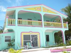 Beach houses lend themselves to different paint jobs, but never saw one quite like this cute pastel one.  Even the canoe matches!  The French screen door and window screen designs are adorable and I love the wide, wide porch on top.  Looks like there ought to be a carousel inside!