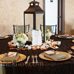 half of the reception tables were decorated with these bronze lanterns anchored by tiny vases of