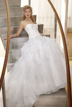 42420-7254WThis beautiful diamond white, strapless wedding dress has a taffeta bodice, asymmetrical tiers organza skirt with scattered embroidered appliques, zip back, and cathedral length train.