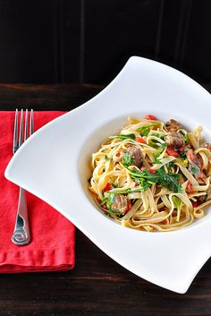 Fettuccine is tossed in a light cream sauce with sausage, roasted red peppers and arugula.  Read More