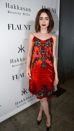 The beautiful Lily Collins is wearing an evening dress that strongly mimics the structure, materials, and design details of a slip. Ready to Wear mimicking under garments is a trend from the early 2000s. Although the slip-style dress isn't that much of a historical reference (early 2000s), her hairstyle is an above the shoulder bob which dates her look further back. She looks like a very fashion forward late 1990s woman. Addy Forte 4/4