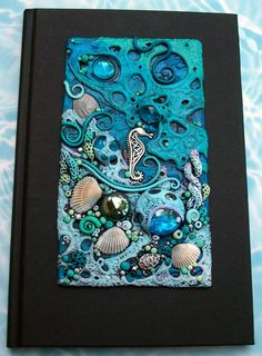 https://flic.kr/p/9US6CJ | Blue Reef Journal | This was a commission for a co-worker. He is taking his wife on a cruise and wanted something in turquoise with an ocean theme. :)  Polymer clay, glass gems, real shells and metal charms.