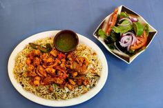 Tender chicken with a spicy pepper coating rests on a bed of rice, and is served with a salad at Derae. (Kyle Kurlick, Special to The Commercial Appeal)
