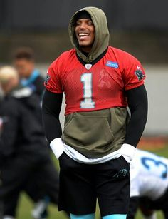 Carolina Panthers quarterback Cam Newton jokes with his teammates during stretching on Thursday, December 17, 2015.