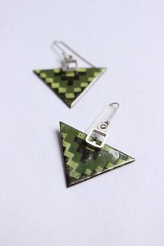 Modern triangular earrings . I´ve cut copper triangles to shape these simple and beautiful earrings. Then Ive applied green, yellow and brown enamels. Both are hanging from a long silver wire.   Materials: Silver 925, copper and enamel. Dimension: Long: 1,8 Width:1,5   ►CARE: The composition of the enamel is ground glass, therefore it is fragile so be careful with the punches.  ►My items are handmade, some subtle variation is due to the craftsmanship that make each unique piece .. any…