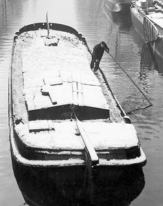 1952. Barge skipper pushes barge through a snowy Prinsengracht in Amsterdam. Photo Kees Scherer. #amsterdam #1952 #Pinsengracht