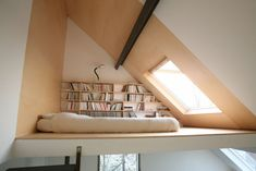 Built-in book shelves under the eaves of a sleeping loft in a Brussels house by Vanden Eackhoudt Freyf Architecture.