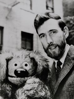 An early Jim Henson & Rowlf the Dog, a scruffy brown dog of indeterminate breed with a rounded black nose and long floppy ears. He was created (and originally performed and voiced) by Jim Henson.