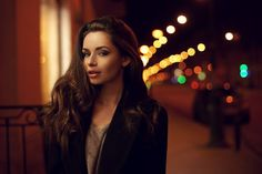 Sexy gorgeous brunette girl portrait in night city lights. Vogue fashion style portrait of young pretty beautiful woman with long dark curly hair. Shallow DOF