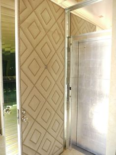 a leather & nail-head front door opens up to a silver-papered elevator entrance