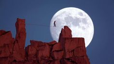 The ultimate full moon shot.  Dean Potter walks a highline at Cathedral Peak as the sun sets and the moon rises.  Shot from over 1 mile away with a Canon 800mm and 2X by Michael Schaefer.  This shot was part of a bigger project for National Geographic called The Man Who Can Fly.  http://channel.nationalgeographic.com/videos/the-man-who-can-fly/