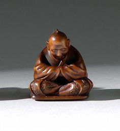 WOOD NETSUKE 19th Century By Sozan. Depicting a seated man wearing a robe with inlaid mon and sporting a lacquer inro with manju. Signed and inlaid with lacquer seal. Height 1.2' (3.1 cm).