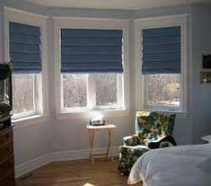 Awkward-shaped windows such as bay windows require extra thought. Here a set of roman shades allows flexible light control for a large bay window.