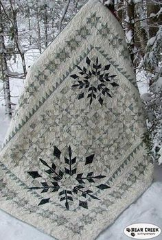 """68"""" x 86"""" - Do you love winter but not the cold? Experience the beauty of winter with this stunning pieced quilt layered with easy to applique snowflakes."""