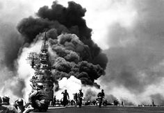 U.S. Navy sailors of the USS Bunker Hill (CV-17) Essex-class aircraft carrier watch the towering flames following the second Japanese kamikaze assault on the ship.