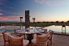 """""""Les Masques"""" de Hamid Binebine, la terrasse se prolongeant vers l'eau, le parcours de golf à perte de vue, les imposantes montagnes de l'Atlas... une parfaite association pour une soirée inoubliable sur l'une de nos meilleures tables.   #AlMaaden"""