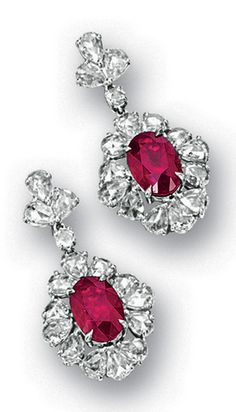 *PAIR OF RUBY AND DIAMOND PENDENT EARRINGS Each centring on an oval ruby altogether weighing approximately 6.65 carats, surrounded by pear-shaped rose-cut diamonds extending to the surmount, spaced by circular rose-cut diamonds, the diamonds altogether weighing approximately 4.00 carats, mounted in 18 karat white gold.